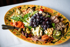 antipasti platter with olives, cheese, grapes and meats